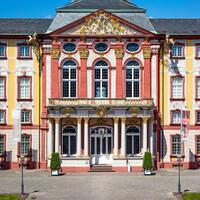 Schloss Bruchsal - Hauptbau - Von Außen / Von Osten / Hofseite - Blick vom Ehrenhof auf die Ostfassade mit dem Mittelrisalit, dem Balkon, dem Fürstensaal und dem Dreiecksgiebel (aufgenommen im Mai 2018, um die Mittagszeit)