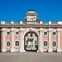 Schloss Bruchsal - Von Außen / Von Westen - Blick vom Ehrenhof auf die Westfassade des Torwachtgebäudes und hinter dem Durchgang auf die Fassade des Kanzleibaus (aufgenommen im Juli 2018, am späten Nachmittag)