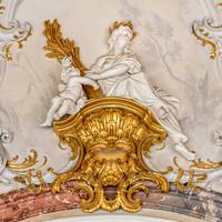 Schloss Bruchsal - Hauptbau / Corps de Logis - Beletage - Marmorsaal / Kaisersaal - Oberhalb des Durchgangs zum Kuppelsaal - Blick auf eine weibliche Figur und eine Putte sowie umgebende Rokoko-Stuckaturen (Stuckaturen ursprünglich von Johann Michael Feichtmayr) (aufgenommen im Februar 2019, am Nachmittag)