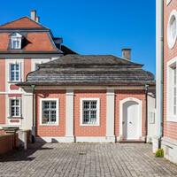 Schloss Bruchsal - Zeughaus / Amtsgreicht - Von Süden - Blick vom Eingang zum Kanzleibau (rechte Seite) auf das Zeughaus (in der Mitte) (nach 1746 errichtet als Gerätelager für die Kommandantenwohnung (linke Seite)) (aufgenommen im Mai 2020, am frühen Nachmittag)