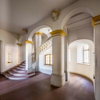 Schloss Bruchsal - Hauptbau / Corps de Logis - Von innen - Nordöstliche Dienertreppe - Erdgeschoss - Von Nordosten - Blick auf die Dienertreppe in das erste Obergeschoss (Zwischengeschoss), links die Tür zur Intrada (aufgenommen im September 2020, am Nachmittag)