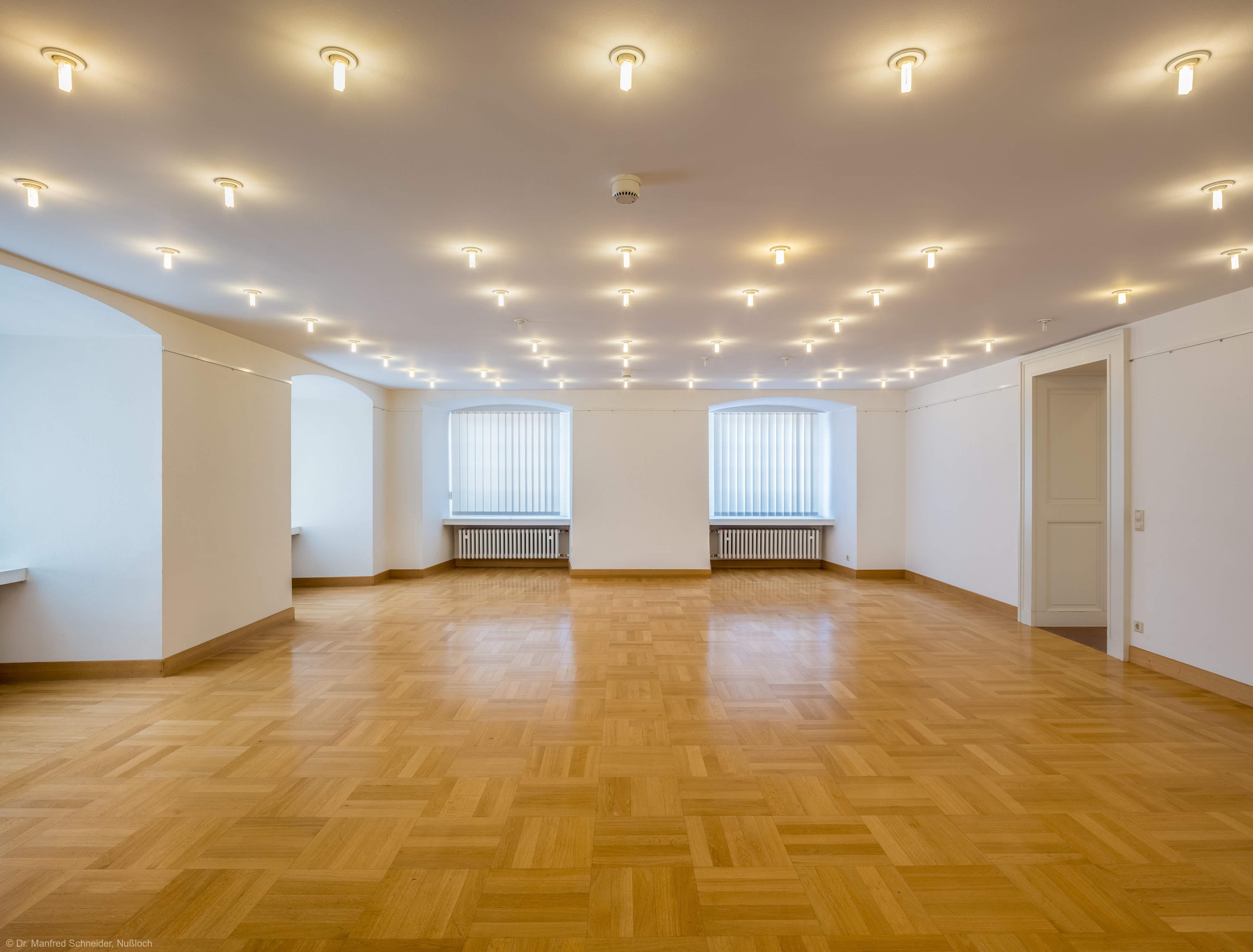 """Schloss Bruchsal - Hauptbau / Corps de Logis - Von innen - Zwischengeschoss / 1. Obergeschoss, Südhälfte - Raum """"Huttensaal"""" (Größe: 63 m², Reihenbestuhlung: max. 40 Personen) - Blick nach Westen in den Raum, rechts die Tür zum Styrumsaal (aufgenommen im Juni 2021, am Nachmittag)"""